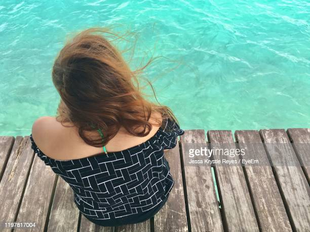 high angle view of woman sitting on plank by sea - jessa stock pictures, royalty-free photos & images