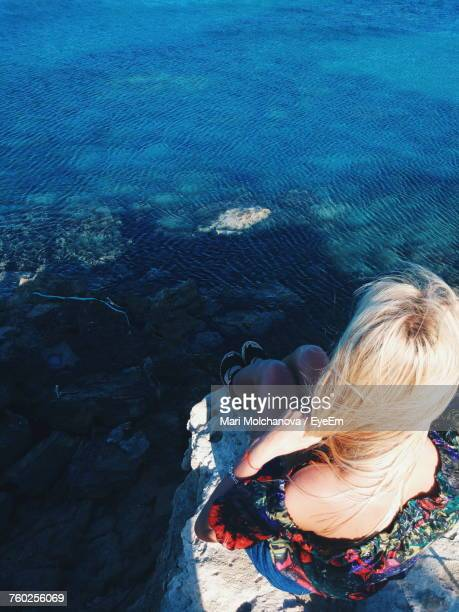 High Angle View Of Woman Sitting On Rock By Sea