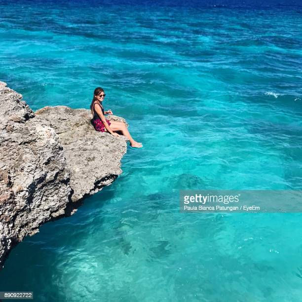 High Angle View Of Woman Sitting On Rock In Sea