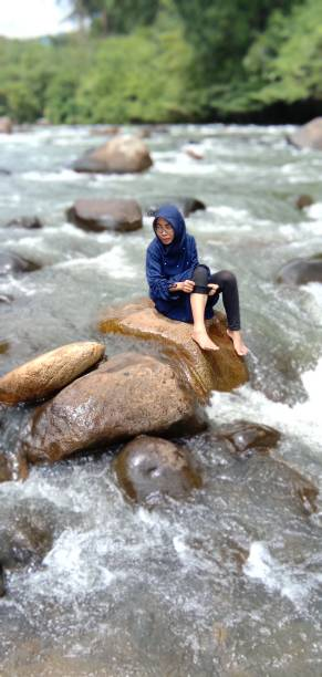 High Angle View Of Woman Sitting On Rock Over River