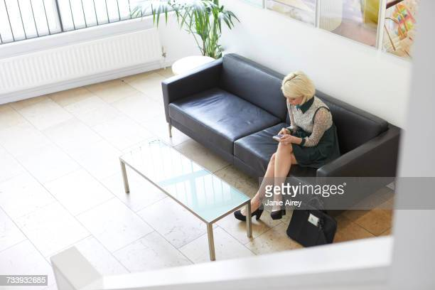 High angle view of woman sitting on sofa in design office lobby