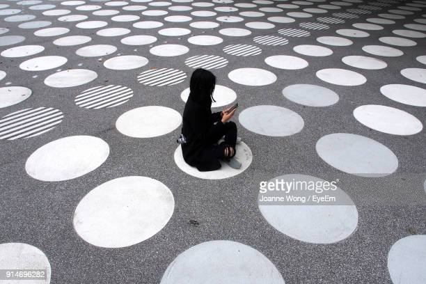 High Angle View Of Woman Sitting On Street