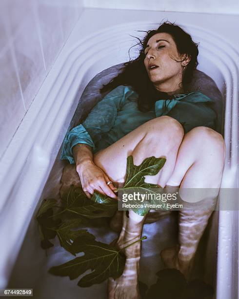 high angle view of woman sleeping in bathtub - passed out drunk stock photos and pictures