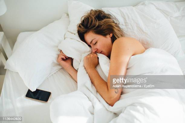 high angle view of woman sleeping on bed - bed stock pictures, royalty-free photos & images