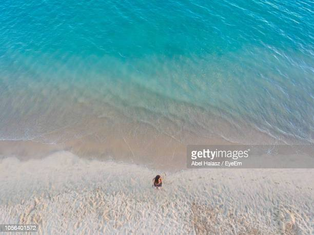high angle view of woman standing at beach - solo adulti foto e immagini stock