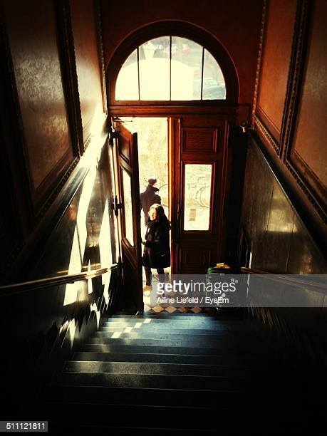 high angle view of woman standing at open door in front of steps - leaving fotografías e imágenes de stock