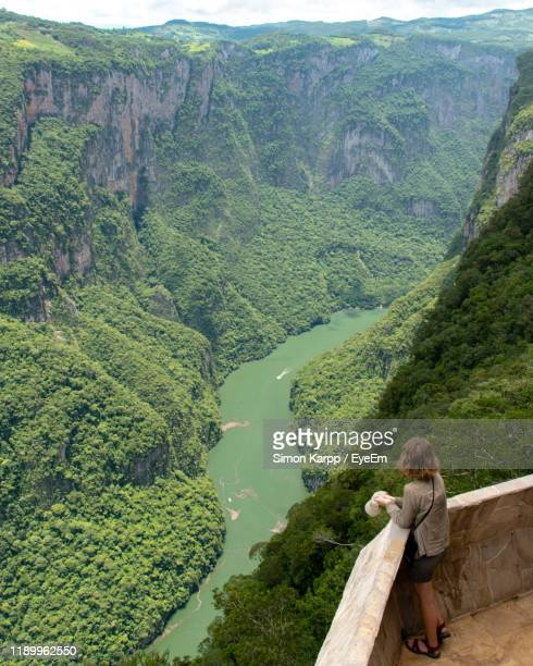 high angle view of woman standing in balcony over river by mountains - chiapas stock pictures, royalty-free photos & images