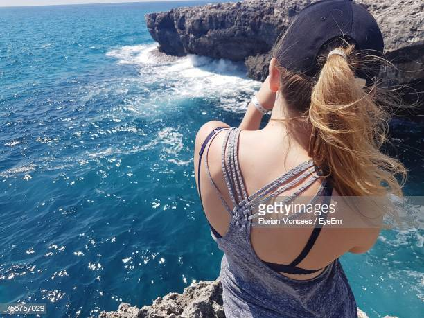 High Angle View Of Woman Standing On Rock Against Sea During Sunny Day