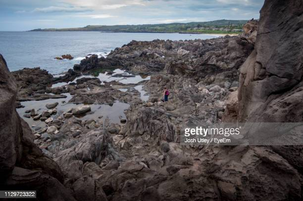high angle view of woman standing on rocky shore - josh utley stock pictures, royalty-free photos & images