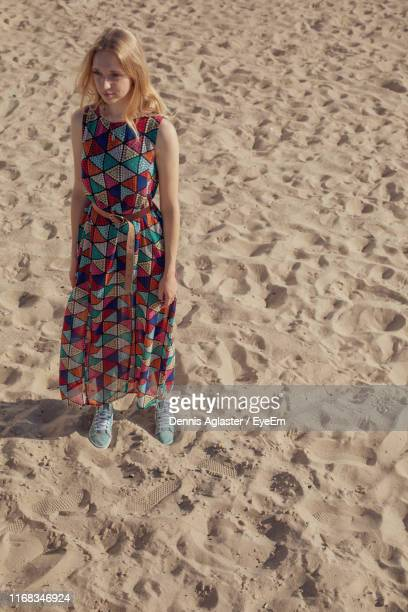 high angle view of woman standing on sand at beach during sunny day - physical position stock pictures, royalty-free photos & images