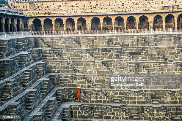 high angle view of woman standing on steps by wall at chand baori - abhaneri stock photos and pictures