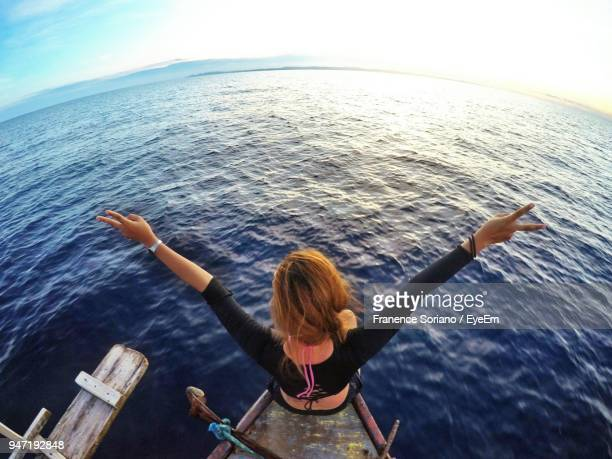 High Angle View Of Woman Standing With Arms Raised On Boat In Sea
