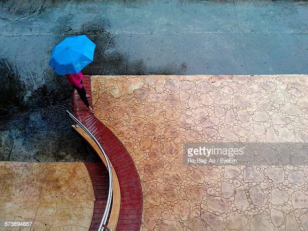 High Angle View Of Woman Standing With Umbrella By Street