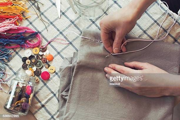 High angle view of woman stitching fabric on table at home