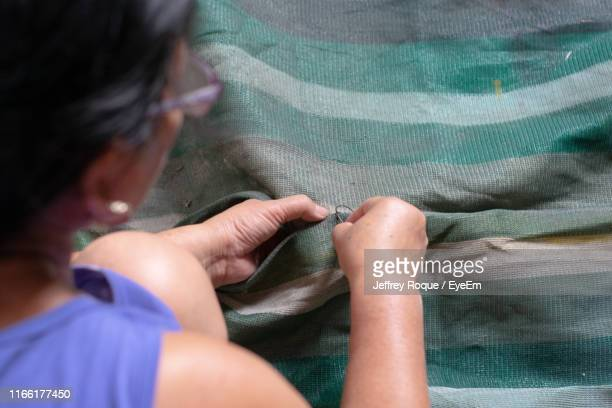 High Angle View Of Woman Stitching Textile