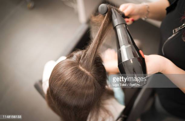 high angle view of woman styling hair - blow drying hair stock pictures, royalty-free photos & images