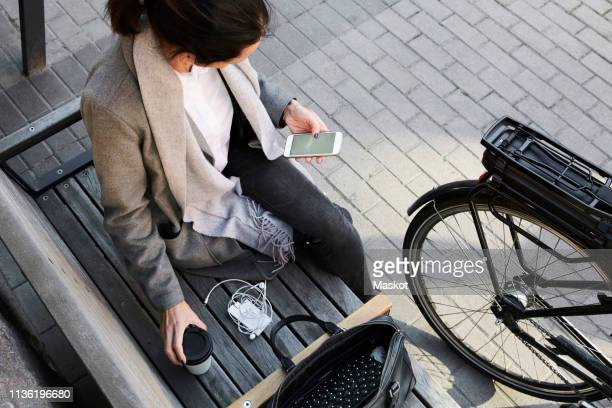 high angle view of woman surfing net through mobile phone while sitting on bench in city - warme dranken stockfoto's en -beelden
