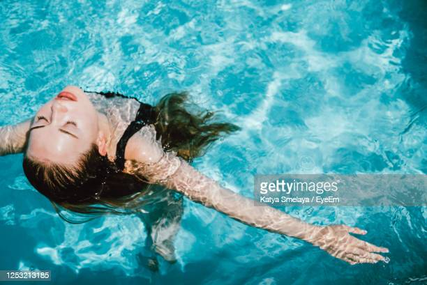 high angle view of woman swimming in pool - 水に浮かぶ ストックフォトと画像
