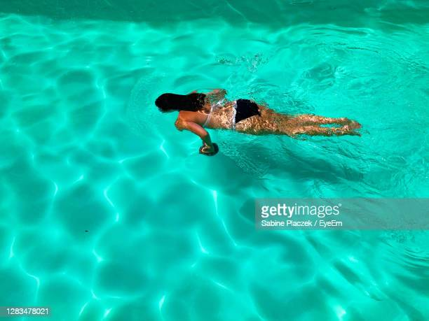 high angle view of woman swimming in pool - underwater stock pictures, royalty-free photos & images
