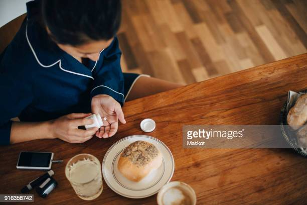 high angle view of woman taking medicine while having breakfast at table - taking a pill stock pictures, royalty-free photos & images