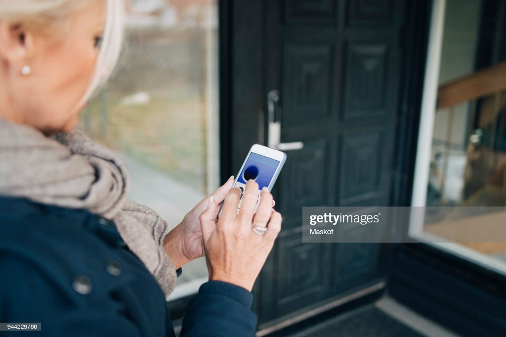 High angle view of woman unlocking house door through smart phone app : Stock Photo