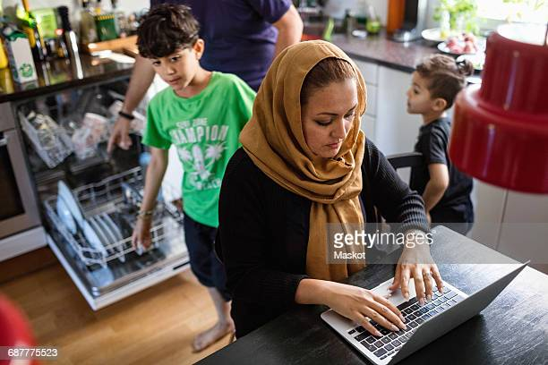 High angle view of woman using laptop on dining table with family working in background at kitchen