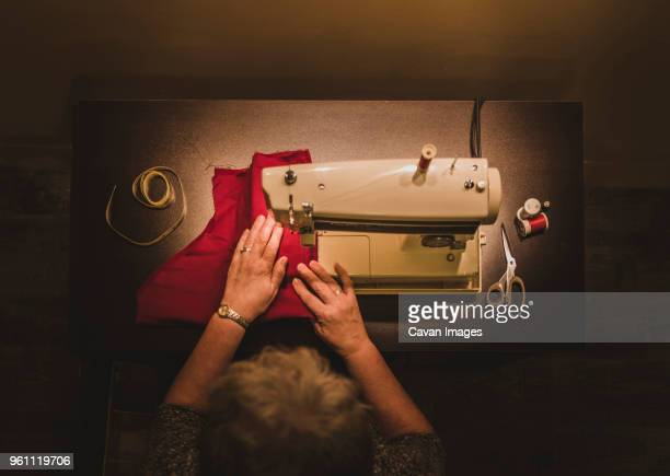 High angle view of woman using sewing machine at workshop
