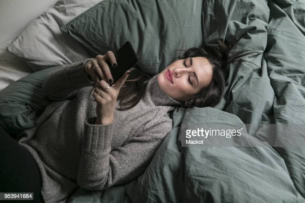 High angle view of woman using smart phone while lying on bed