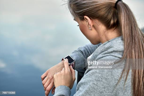 High angle view of woman using smart watch against lake