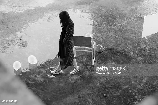High Angle View Of Woman Walking By Balloons On Puddle