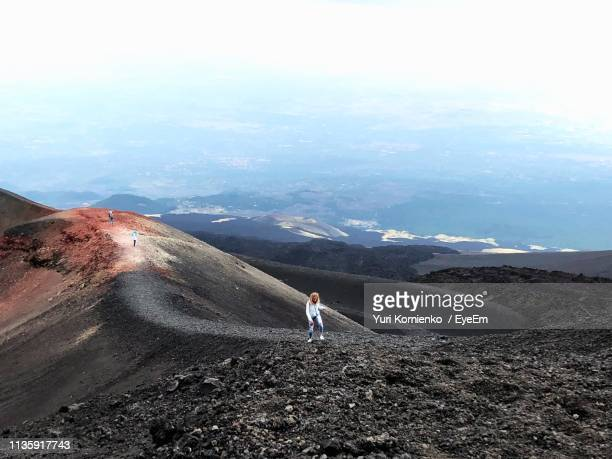 high angle view of woman walking on mountain against sky - mt etna stock pictures, royalty-free photos & images