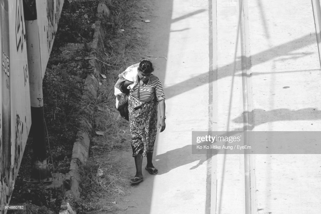 High Angle View Of Woman Walking On Road : Stock Photo