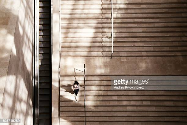 high angle view of woman walking on staircase - degraus e escadas - fotografias e filmes do acervo