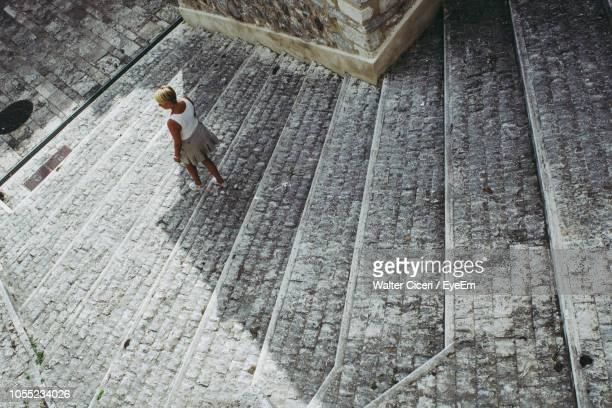 high angle view of woman walking on steps - walter ciceri foto e immagini stock