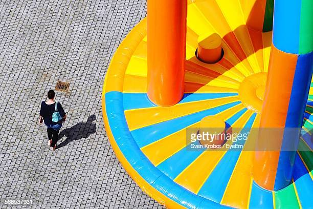 High Angle View Of Woman Walking On Street With Bouncy Castle