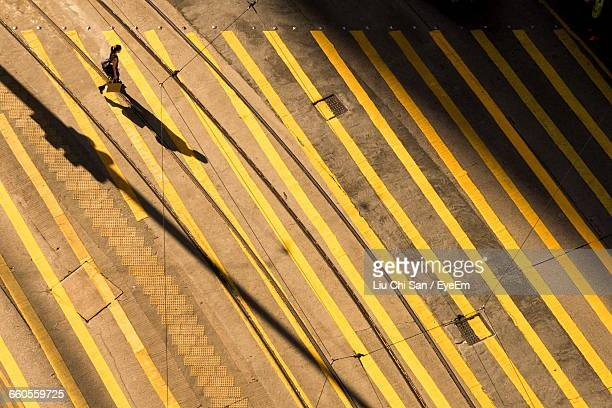 High Angle View Of Woman Walking On Yellow Striped Street