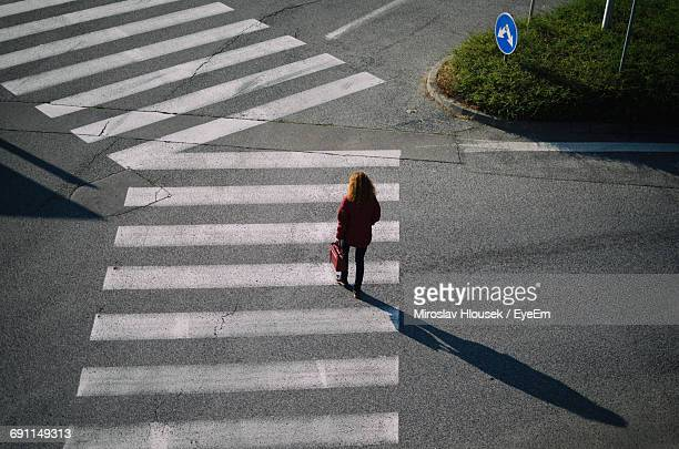 high angle view of woman walking on zebra crossing at street - zebra crossing stock photos and pictures