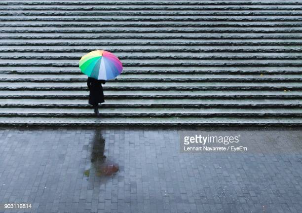 High Angle View Of Woman Walking With Umbrella