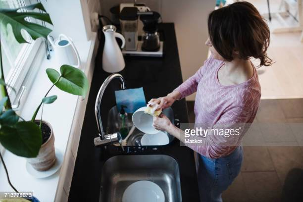 High angle view of woman washing dishes in kitchen at home