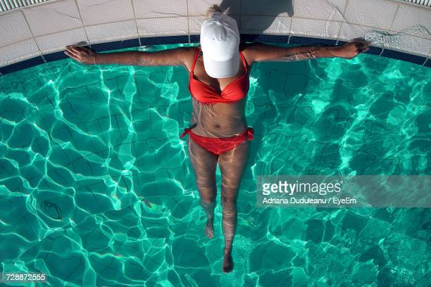 high angle view of woman wearing bikini relaxing in swimming pool - adriana duduleanu stock photos and pictures