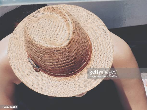 high angle view of woman wearing hat while sitting outdoors - straw hat stock pictures, royalty-free photos & images