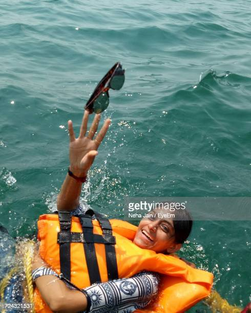 High Angle View Of Woman Wearing Life Jacket Swimming In Sea