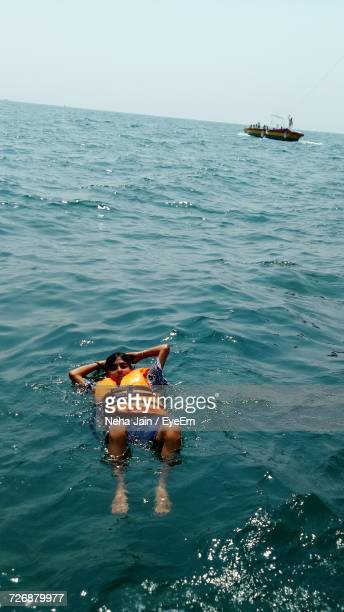 High Angle View Of Woman Wearing Life Jacket While Swimming In Sea
