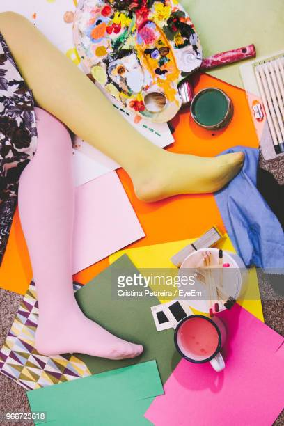 high angle view of woman wearing stockings while lying on messy bed - パンティストッキング ストックフォトと画像