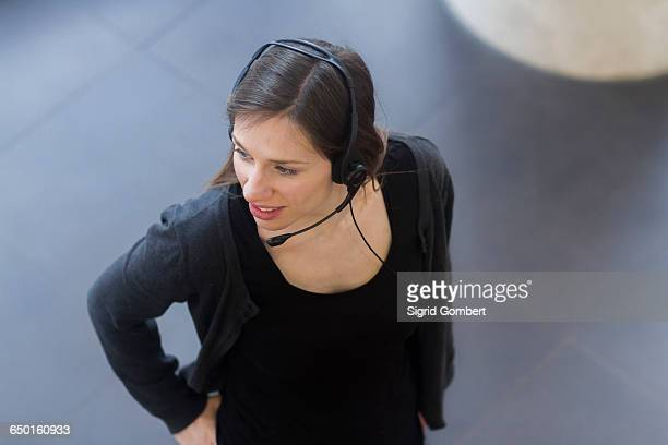 high angle view of woman wearing telephone headset looking away - sigrid gombert stock pictures, royalty-free photos & images