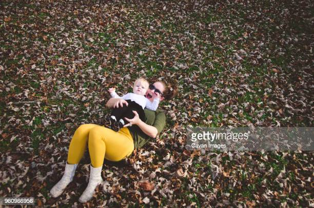 High angle view of woman with baby girl lying on dry leaves at field