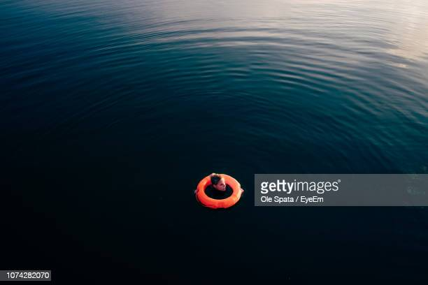 high angle view of woman with life belt swimming in lake - sicherheit stock-fotos und bilder