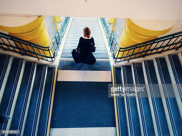 High Angle View Of Woman With Luggage Moving Down On Steps In Building