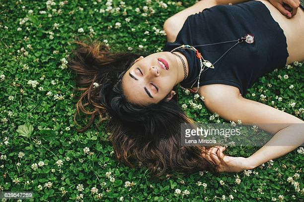 high angle view of woman with nose ring lying on clover covered grass, eyes closed - crop top stock pictures, royalty-free photos & images