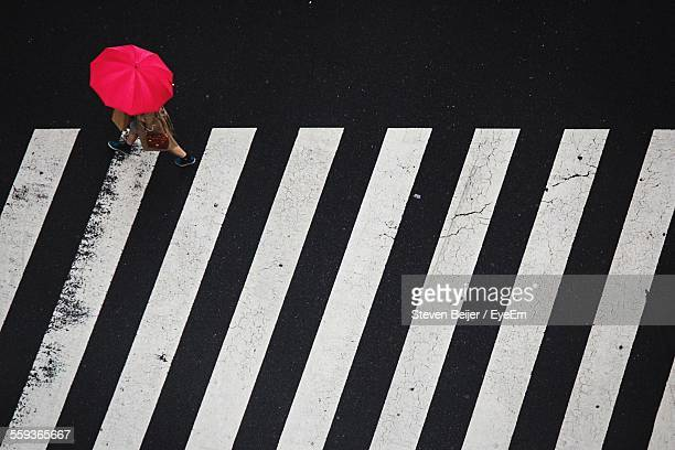 High Angle View Of Woman With Red Umbrella Walking Over Zebra Crossing